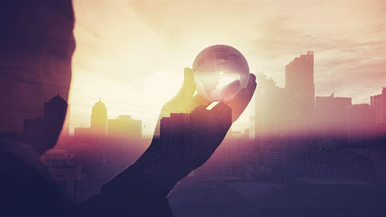 phantom figure of a businessman holding a crystal ball out towards a city skyline