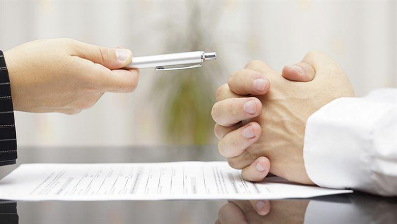 a hand holding out a pen over a contract
