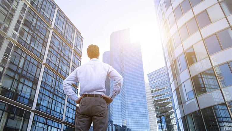 a man looking up at several tall office buildings