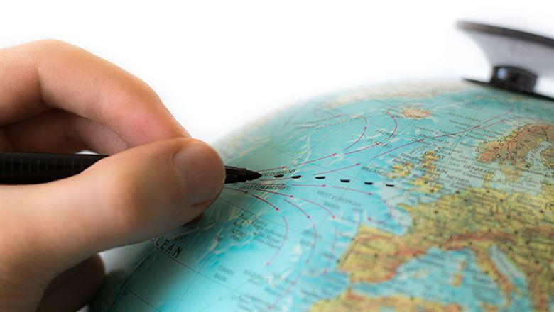 a hand drawing a connecting line on a globe