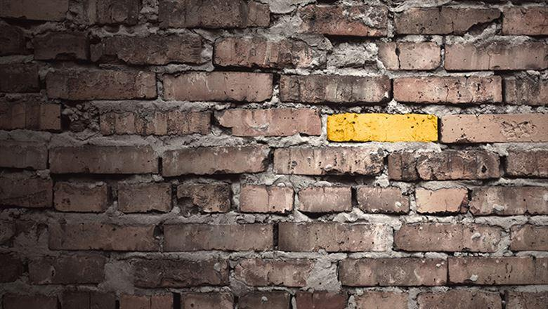 a yellow brick standing out from other bricks on a wall
