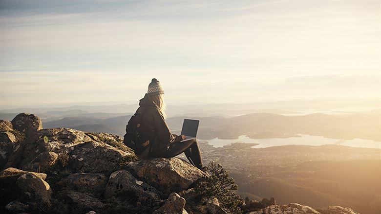 a person using a laptop while looking out over a mountain view