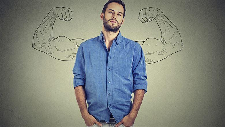 man standing confidently with muscle arms drawn behind him