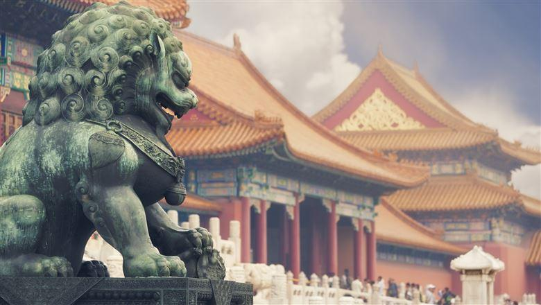 Chinese statue with traditional architecture in the background