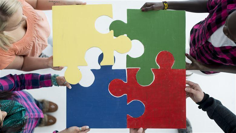people putting four puzzle pieces together