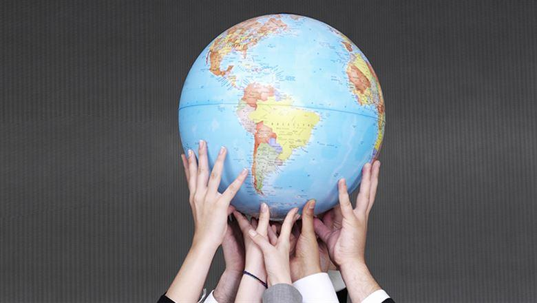 different hands holding up a globe
