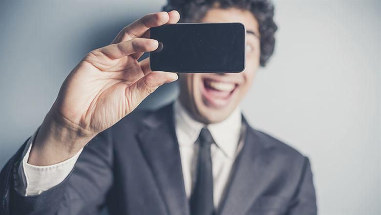 young professional with a big smile taking a selfie