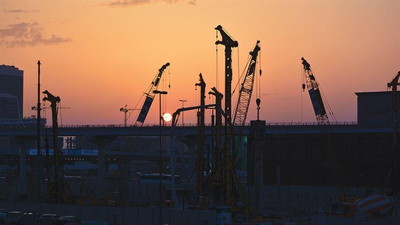 sunset in Dubai with cranes on skyline
